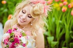 一个非常美丽的新娘金发碧眼的女人的画象一件白色礼服的与 库存照片