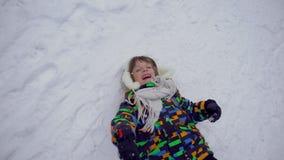 一个非常逗人喜爱的愉快的小男孩在公园在冬天 花雪时间冬天 愉快的男孩获得乐趣在雪冬天公园 他是愉快的 股票录像