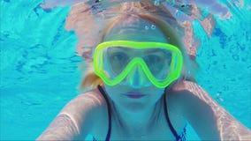 一个面具的一个少妇潜水的看照相机在水下 头发在光芒的水中美妙地漂浮 股票录像
