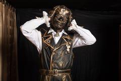 一个面具的人在靠机械装置维持生命的人服装 库存图片