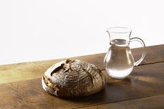 一个面包和一个水罐在桌上的水 免版税库存图片