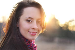 一个面孔美好的女性模型的图象在一个五颜六色的棉花围巾特写镜头的在日落背景 图库摄影