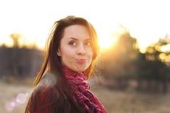 一个面孔美好的女性模型的图象在一个五颜六色的棉花围巾特写镜头的在日落背景 免版税库存照片