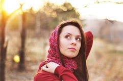 一个面孔美好的女性模型的图象在一个五颜六色的棉花围巾特写镜头的在日落背景 免版税库存图片