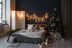 一个顶楼样式的一间宽敞卧室与一棵装饰的圣诞树和诗歌选 免版税库存照片