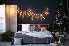 一个顶楼样式的一间宽敞卧室与一棵装饰的圣诞树和诗歌选 免版税图库摄影