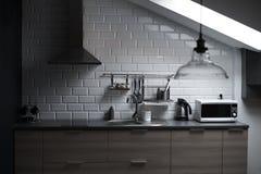 一个顶楼样式的厨房与混凝土和砖墙和瓦片、水槽、出气孔、微波、茶壶和一盏现代灯 免版税库存图片