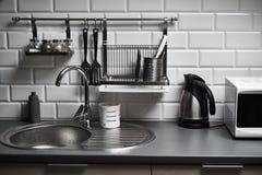 一个顶楼样式的厨房与混凝土和砖墙和瓦片、水槽、微波、茶壶和一盏现代灯 免版税库存照片
