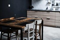 一个顶楼样式的厨房与混凝土和砖墙和瓦片 有与白色椅子的黑厨房用桌 库存照片