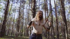 一个顽固的家伙在森林投掷从接近的一把刀子 刀子把戏 人有长发和一条辫子在他的胡子 股票录像