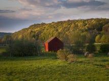 一个领域的一点红色谷仓春天 免版税库存照片