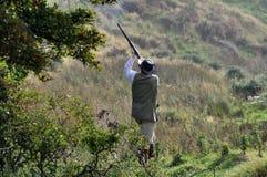 一个领域的人在鸭子射击射击低头与猎枪 免版税库存图片