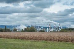 一个领域的化工工厂与多云天空 免版税库存图片