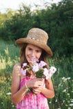 一个领域的女孩与花 免版税图库摄影