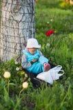 一个领域的小女孩孩子与绿草和开花的郁金香 免版税图库摄影