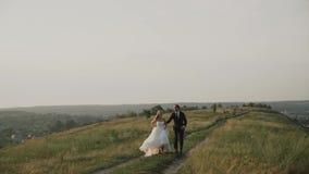 一个领域的恋人在日落 跑在领域附近的人和女孩在日落 夫妇愉快微笑 股票视频