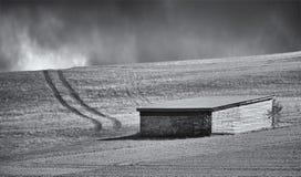 一个领域的木棚子与带领往与不祥的黑暗的云彩的天际的车轨道在距离 图库摄影