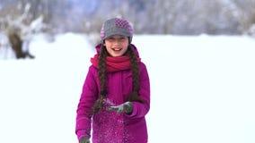 一个领域的美丽的小女孩在雪 从的打击雪手掌 股票录像