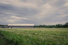 一个领域的谷仓在多云天气 库存照片