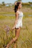 一个领域的年轻美丽的女孩与在白色sundress的花 免版税库存图片