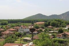一个风景包括一座遥远的山、Todorov将军村庄和鹳许多元素 免版税库存图片