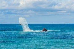一个飞行板车手的剪影海上的 专业车手在蓝色盐水湖把戏 热带水体育设备 图库摄影