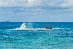 一个飞行板车手的剪影海上的 专业车手在蓝色盐水湖把戏 热带水体育设备 免版税图库摄影