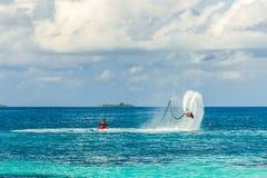 一个飞行板车手的剪影海上的 专业车手在蓝色盐水湖把戏 热带水体育设备 库存照片