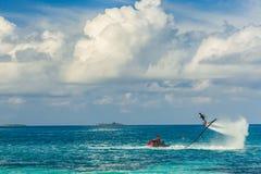 一个飞行板车手的剪影海上的 专业车手在蓝色盐水湖把戏 热带水体育设备 库存图片