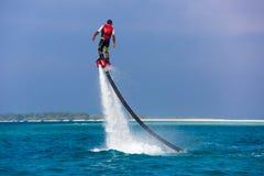 一个飞行板车手的剪影海上的 专业车手在蓝色盐水湖把戏 热带水体育设备 免版税库存图片