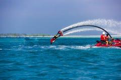 一个飞行板车手的剪影海上的 专业车手在蓝色盐水湖把戏 热带水体育设备 免版税库存照片