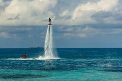 一个飞行板车手的剪影海上的 图库摄影