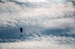 一个飞行滑翔伞的剪影反对云彩背景的  库存照片