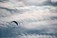 一个飞行滑翔伞的剪影反对云彩背景的  库存图片