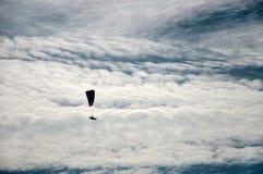 一个飞行滑翔伞的剪影反对云彩背景的  免版税库存图片