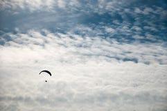 一个飞行滑翔伞的剪影反对云彩背景的  图库摄影