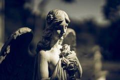 一个飞过的天使的雕象在黑暗的 库存图片