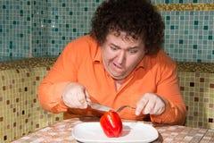 一个饥饿的人和一块板材有一棵菜的 免版税库存照片