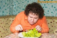 一个饥饿的人和一块板材有一棵菜的 库存照片