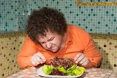 一个饥饿的人和一块板材有一棵菜的 免版税库存图片