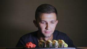 一个饥饿的人看寿司,不吃,等待 股票视频