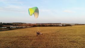 一个马达滑翔伞的飞行在领域的反对湖 股票录像