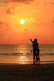 一个骑自行车的人的剪影海滩的 库存照片
