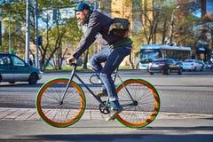 一个骑自行车者在城市在一条行人交叉路去 环境友好的运输方式 免版税库存照片