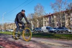 一个骑自行车者在城市沿自行车道路移动 环境友好的运输方式 库存图片
