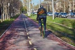 一个骑自行车者在城市沿自行车道路移动 环境友好的运输方式 图库摄影