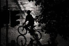 一个骑自行车者的剪影在雨中 图库摄影