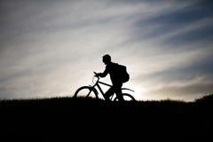 一个骑自行车者的剪影山的 库存照片