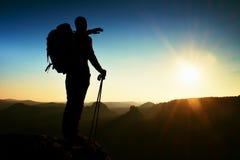 一个高人的锋利的剪影在山的上面的与太阳的在框架 在山的旅游指南 免版税库存图片