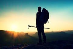 一个高人的锋利的剪影在山的上面的与太阳的在框架 在山的旅游指南 库存图片